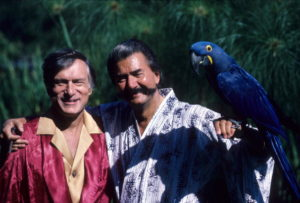 "Portrait of celebrity artist LeRoy Neiman and Playboy editor Hugh Hefner posing with macaw ""Macbeth"" during photo shoot at the Playboy Mansion in Holmby Hills neighborhood. Los Angeles, CA 9/22/1985 CREDIT: Peter Read Miller (Photo by Peter Read Miller /Sports Illustrated/Getty Images)"
